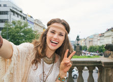 Hippy woman tourist making selfie in Prague and showing victory. Cheerful longhaired hippy-looking woman tourist showing victory gesture while making selfie in Stock Photo