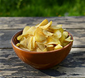 Сhips on old wooden table. Chips in a plate on old wooden table Royalty Free Stock Photography