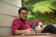 Hipser при компьтер-книжка связывая через smartphone Стоковая Фотография