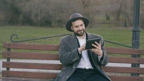 Hipser creatieve bedrijfsmens in hoed gebruikend de computer van tabletpc en zittend op de bank van de stadsstraat in park tijden stock footage