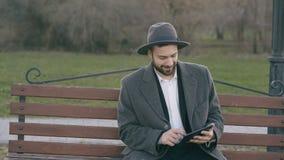 Hipser creatieve bedrijfsmens in hoed gebruikend de computer van tabletpc en zittend op de bank van de stadsstraat in park tijden stock video