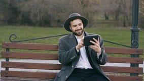 Hipser parkerar den idérika affärsmannen i hatt genom att använda minnestavlaPCdatoren och sitta på stadsgatabänk in under avbrot royaltyfri bild