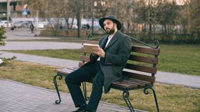 Hipser parkerar den idérika konstnärmannen i hatt- och lagteckning med penn- och sketchbooksammanträde på stadsgatabänk på arkivfoton