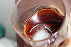 Hipster överexponerat exponeringsglas av whisky på is royaltyfria bilder