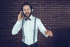 Hipster με τις προσοχές ιδιαίτερες απόλαυση της μουσικής ακούσματος Στοκ Εικόνες