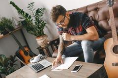 Νέος κιθαρίστας hipster στο σπίτι με τις σημειώσεις γραψίματος κιθάρων στοχαστικές στοκ φωτογραφίες