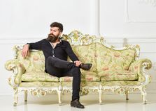 Hipster on arrogant face sits alone. Man with beard and mustache spends leisure in luxury living room. Rich and lonely. Concept. Owner of luxury apartment sits royalty free stock photos