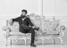 Hipster on arrogant face sits alone. Man with beard and mustache spends leisure in luxury living room. Rich and lonely stock image