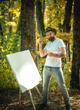 Hipster artist in a hat creating art in the woods. Art concept. Painting in nature. Start new picture. Painter with. Easel and canvas royalty free stock photography
