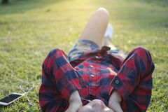 Hipster Asian woman wearing red tone shirt lying on the green grass for relaxing while listening the music Royalty Free Stock Images