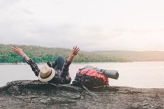 Hipster asian young girl with backpack enjoying sunset on peak mountain. Travel Lifestyle adventure concept. Vacations into the wild stock images