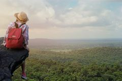 Hipster asian young girl with backpack enjoying sunset on peak mountain. Travel Lifestyle adventure concept. Vacations into the wild stock photos