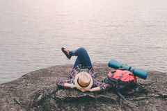 Hipster asian young girl with backpack enjoying sunset on peak mountain. Travel Lifestyle adventure concept. Vacations into the wild royalty free stock photography