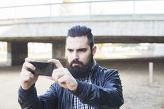 Hipster attractive modern man makes a selfie. stock image