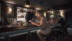 Hipster bartender combining ingredients and making cocktails in bar while young upset woman sits near bar counter and