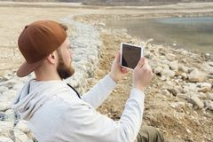 Hipster with a beard in a cap and a sweatshirt with a tablet in his hands takes pictures on a tablet while being on the. Nature by the lake Royalty Free Stock Photography