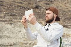 Hipster with a beard in a cap and a sweatshirt with a tablet in his hands takes pictures on a tablet while being. Outdoors Stock Image