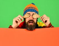 Hipster with beard and confused face closes eyes with leaf. Autumn and cold weather concept. Man in hat holds oak tree leaves on green and orange background royalty free stock photography