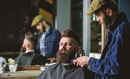 Hipster with beard covered with cape trimming by professional barber in stylish barbershop. Barber busy with grooming royalty free stock image