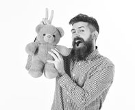 Hipster with beard or father plays with teddy bear or plush toy. Fatherhood concept. Man with happy face holds soft toy. Or teddy bear in hand on white Royalty Free Stock Photo