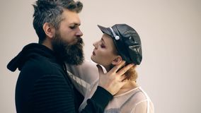 Hipster with beard and girl in leather cap and gloves. Couple in love of sexy woman and bearded man. Rock couple embrace. On grey background. Friendship and stock footage