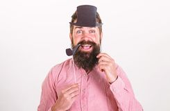 Hipster with beard and mustache on happy face posing with photo booth props. Guy smokes tobacco pipe. Aristocracy. Concept. Man holding paper party props stock photo