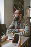 Hipster with beard with smartphone and laptop on table giving in Stock Image