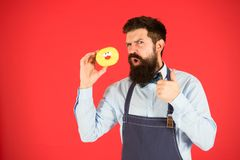 Hipster bearded baker hold glazed donut on red background. Cafe and bakery concept. Sweet donut from baker. Man bearded royalty free stock photos