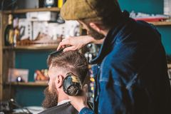 Hipster bearded client getting hairstyle. Barber with hairdryer drying and styling hair of client. Barber with hairdryer royalty free stock photos