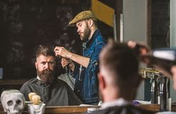 Hipster bearded client getting hairstyle. Barber with hairdryer works on hairstyle for bearded man, barbershop royalty free stock photo