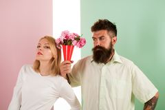 Hipster bearded give bouquet flowers girl excuse gesture. Man with beard apologyes woman. Couple date bouquet flowers. Gift. Apology concept. Couple in love royalty free stock photo