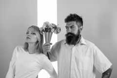 Hipster bearded give bouquet flowers girl excuse gesture. Man with beard apologyes woman. Couple date bouquet flowers. Gift. Apology concept. Couple in love royalty free stock image