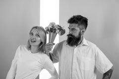 Hipster bearded give bouquet flowers girl excuse gesture. Man with beard apologyes woman. Couple in love problem. Relations forgive guilty boyfriend. Couple royalty free stock images