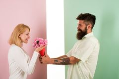 Hipster bearded give bouquet flowers to girlfriend. Man with beard congratulates woman birthday anniversary holiday stock photos