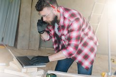 Hipster bearded man is carpenter, builder, designer stands in wo. Rkshop, using laptop and talking on cell phone.On desk is construction tools, in background royalty free stock photo
