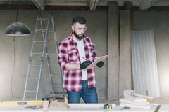 Hipster bearded man is carpenter, builder, designer stands in wo. Rkshop, holds clipboard and takes notes. On desk is construction tools, in background royalty free stock photography