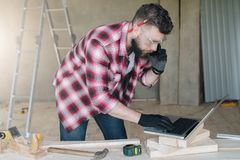 Hipster bearded man is carpenter, builder, designer stands in wo. Rkshop, using laptop and talking on cell phone.On desk is construction tools, in background stock images