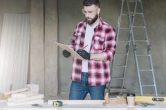 Hipster bearded man is carpenter, builder, designer stands in wo. Rkshop, holds clipboard and takes notes. On desk is construction tools, in background stock photos