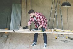 Hipster bearded man is carpenter, builder, designer stands in workshop, using laptop. On desk is construction tools. In background stepladder. Repair royalty free stock image