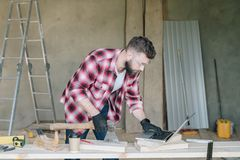 Hipster bearded man is carpenter, builder, designer stands in workshop, using laptop. On desk is construction tools. In background stepladder. Repair Stock Images