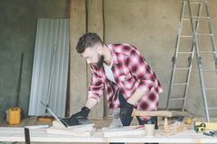 Hipster bearded man is carpenter, builder, designer stands in workshop, using laptop, holding an ax. On desk is construction tools, in background stepladder royalty free stock image