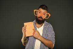 Hipster bearded man funny eyeglasses hold notepad or book. Read this book. Comic and humor sense. Courses adult. Education. Self education concept. Literary royalty free stock image