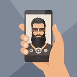 Hipster bearded man lumberjack takes selfie using a smartphone. Royalty Free Stock Image