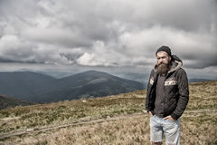 Hipster, bearded man on mountain top on natural cloudy sky. Hipster, bearded man, long beard, brutal caucasian with moustache, unshaven guy in jacket with royalty free stock photos