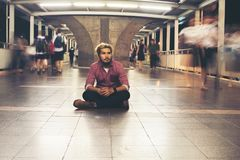 Hipster bearded man sitting on the floor while traveling at nigh. T. Feel lonely to traveling alone background royalty free stock photos