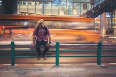 Hipster bearded man sitting on railing with car motion background while traveling at night. Hipster bearded man sitting on railing with car motion background stock images