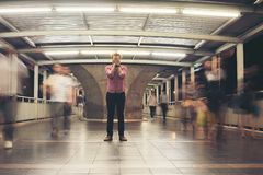 Hipster bearded man standing on the floor with people motion background while traveling at night. Hipster bearded man standing on the floor with people motion royalty free stock photography