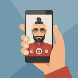 Hipster bearded young man takes selfie using a smartphone. Royalty Free Stock Photos
