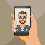 Hipster bearded young man takes selfie using a smartphone. Royalty Free Stock Photography