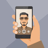 Hipster bearded young man takes selfie using a smartphone. Stock Photography